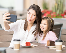 Mother and daughter taking a selfie with tongues sticking out